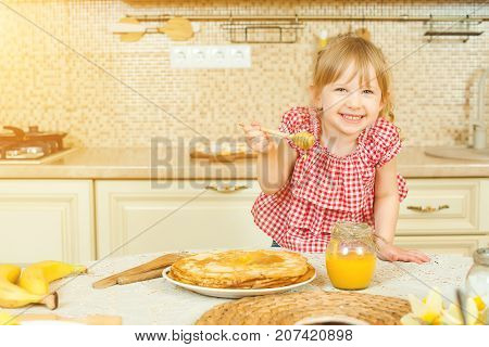 Cute Little Girl Prepare Pancakes And Pouring Honey On Stack Of Pancakes.