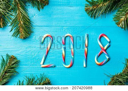 Image of Christmas caramel sticks in form of numbers. New year 2018. Blue wooden table with spruce branches