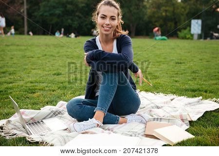 Portrait of a smiling young female student sitting on the grass with laptop and textbooks and looking at camera outdoors