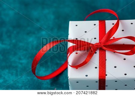Elegant Gift Box Wrapped in Grey Silver Paper with Polka Dots Red Ribbon on Blue Background. Christmas New Years Presents Shopping Sale. Copy Space