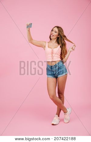Full length portrait of young funny readhead woman in summer wear makes selfie on smartphone, over pink background