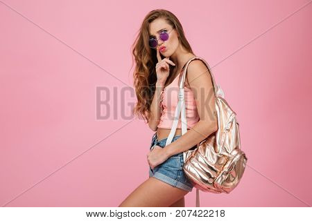 Close up of young beautiful readhead thinking woman with metallic backpack, over pink background
