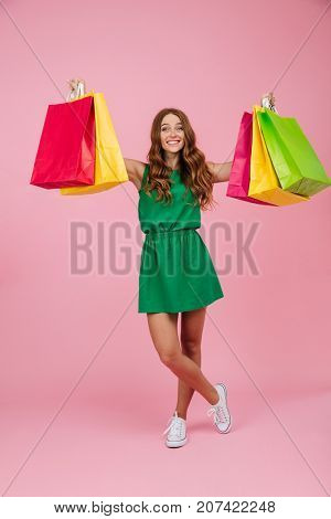 Portrait of young cheerful readhead curly woman in green dress, holding colourful shopping bags, isolated over pink background