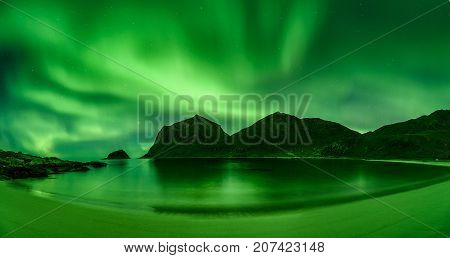 Haukland beach in the Lofoten islands in Norway with strong green northern lights also known as Aurora Borealis