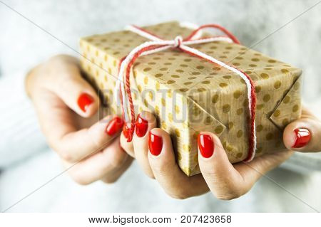 Christmas gift wrapped in craft paper in polka dots in female hands with red manicure