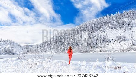 A young girl admires the winter landscape on the lake. Beautiful lake Amut in taiga hills on Far East of Russia in early october. Mountain lake in winter. Beautiful nature. Snowy weather.