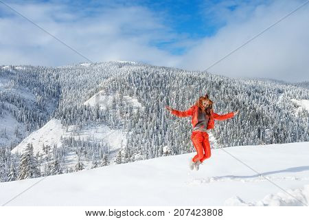 A young happy girl enjoys beauty of winter landscape near beautiful lake Amut in taiga hills on Far East of Russia in early october.