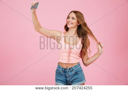 Close-up portrait of young cheerful readhead woman in summer wear makes selfie on smartphone, over pink background
