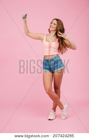 Full length portrait of young smiling readhead woman in summer wear makes selfie on smartphone, showing peace sign, over pink background