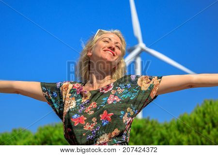 Portrait of blonde woman with open arms enjoying for modern power technology of wind turbines. Sagres, Algarve in Portugal.Alternative energy, renewable energy and environmental sustainability concept