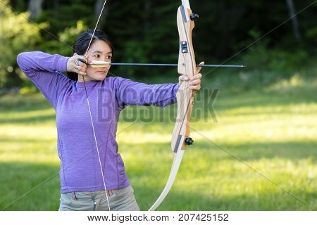 Female Athlete Aiming With Bow And Arrow In Forest