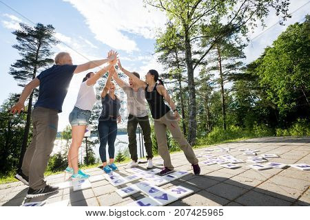 Friends Giving High-Five After Solving Crossword Puzzle On Patio