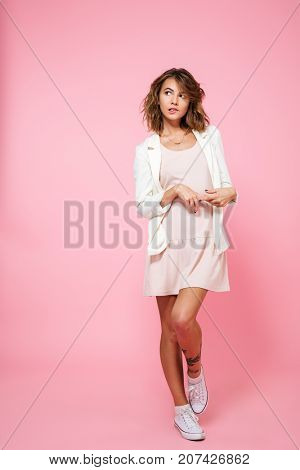 Full length portrait of an embarrassed shy girl in summer dress posing while standing on one foot and looking away at copy space isolated over pink background