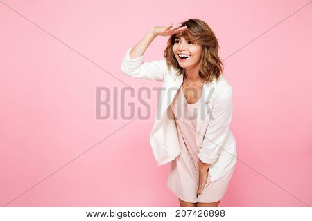 Portrait of a smiling cheerful girl in summer clothes looking far away with hand at her forehead isolated over pink background