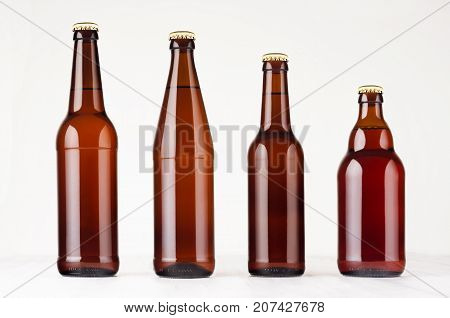 Collection different brown beer bottles mockup. Template for advertising design branding identity on white wood table.