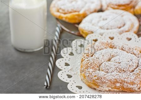 Swirl Danish Pastry Powdered on Cooling Rack and Cake Stand. Bottle of Milk Striped Straw. Dark Tabletop.