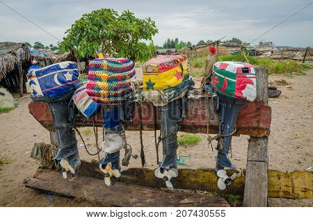 Colorful lined up fishing boat engines with artistic covers on wooden stand, The Gambia, West Africa.