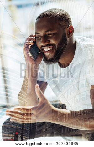 Cheerful conversation. Smiling young bearded man with a short haircut talking on the phone while sitting and waving left hand