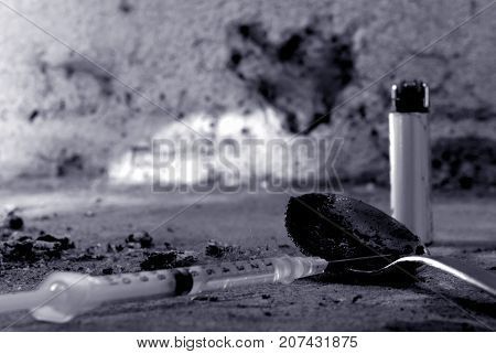 Close up of dirty spoon, drug syringe and lighter in very filthy surface. Heart-shaped hole in the wall on background. Black and white image with space for text.