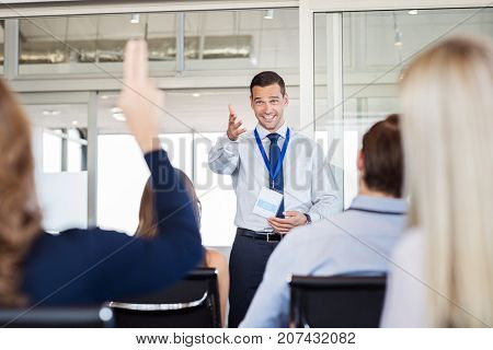 Businessman in seminar pointing towards woman raising hand to say a question. Human resource manager training new company employees. Businesswoman raising hand at conference to answer a question.