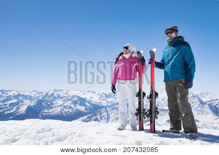 Happy couple in winter clothes holding red ski on snow. Smiling couple standing on mountain top together. Man and woman holding ski in beautiful snowy landscape with copy space.