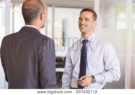Two businessmen having happy conversation in office. Employee talking to boss discussing about new project. Mid adult businessman meeting senior manager in a modern office.