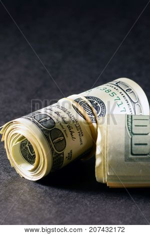 Money rolls on dark surface and background. Vertical image.
