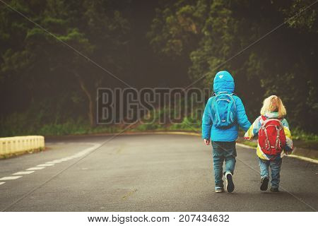 kids go to school - brother and sister with backpacks walking on the road