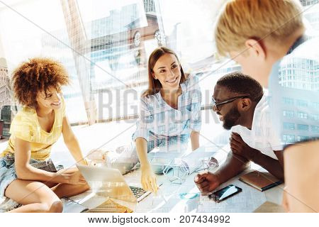 Positive day. Close up of intelligent enthusiastic groupmates discussing studying while looking at each other and smiling