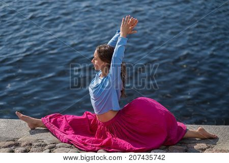 Yoga outdoors. Sporty fit caucasian woman in red skirt doing hanumanasana pose posture in nature
