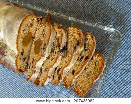 Top view of slices of homemade Christmas stollen cake with raisins, nuts, spices and chopped dried fruit on blue tablecloth