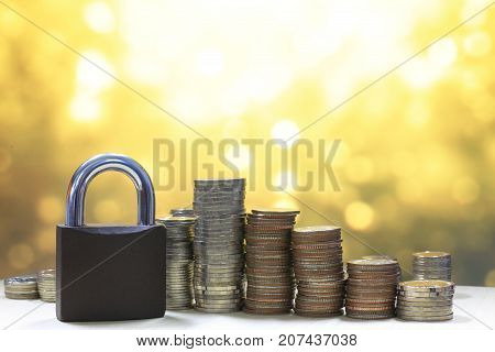 Coin money stack and lock, on gold light background. Saving and financial security concept.