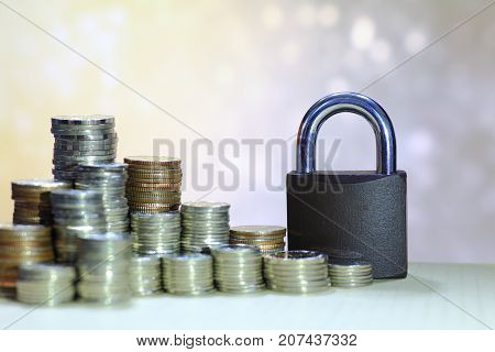 Coin money stack and lock, on yellow and white light background. Saving and financial security concept.