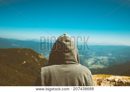 Unrecognizable female person standing at high mountain viewpoint. Rear view of young adult woman wearing hoodie looking at distance on horizon. Toned image.