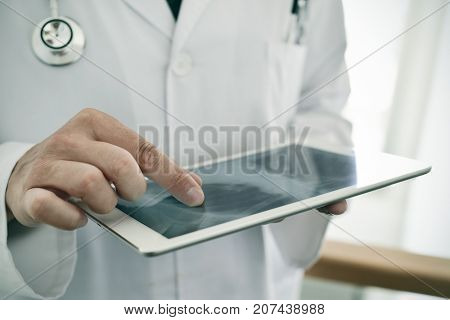closeup of a young caucasian doctor man wearing a white coat checking a chest radiograph in a tablet computer