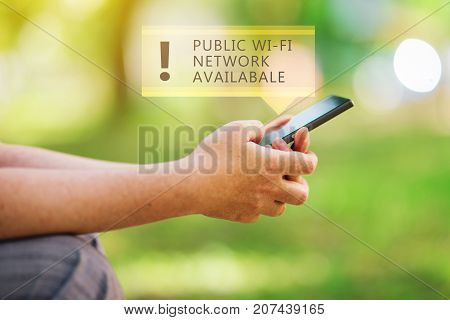 Public wi-fi network available message on smartphone in female hands wireless internet hotspot in park