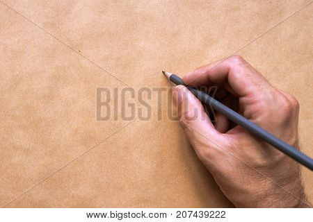 Male illustrator and sketch artist drawing with pencil top view of hand close up with selective focus