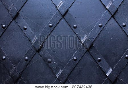 Slashed black painted iron door with steel stripes.
