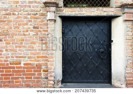 Black iron door with riveted stripes in an old red brick wall.