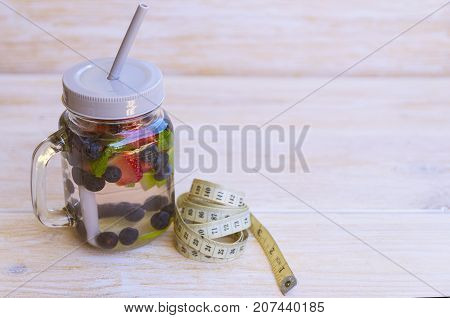 Detox infused water with lime strawberries blueberries and mint in mason jar with centimeter on wooden background. Cleansing drink to lose weight. Healthy lifestyle detox diet concept.