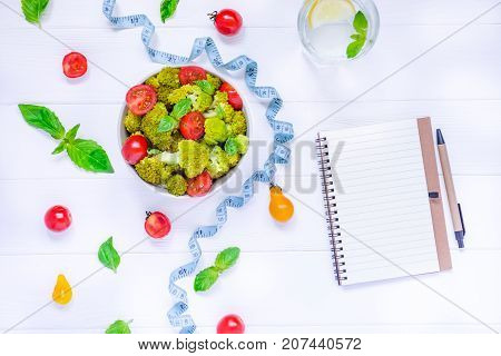 Top View Salad Bowl With Cherry Tomatoes, Broccoli, Measuring Tape And Diet Book On The White Wooden
