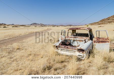 Wreck of abandoned classic car in between dry grass next to dirt road in Damaraland with Brandberg mountain in background, Namibia, Southern Africa.