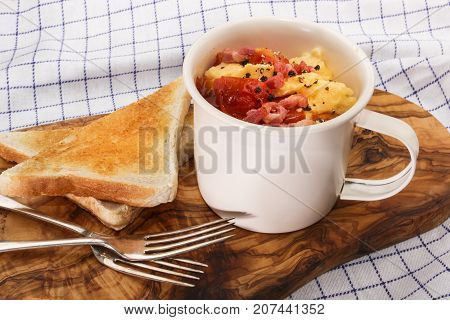 scrambled eggs with tomatoes and fried bacon in a cup also some toast
