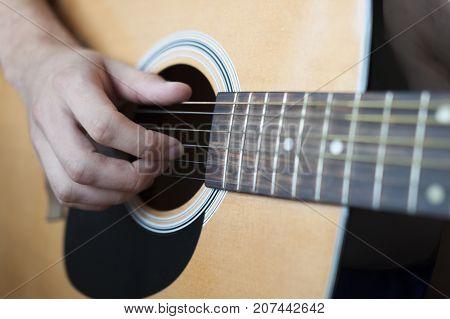 Man plays an acoustic guitar. Acoustic guitar close-up.