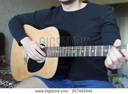 A man plays an acoustic guitar. Acoustic guitar close-up
