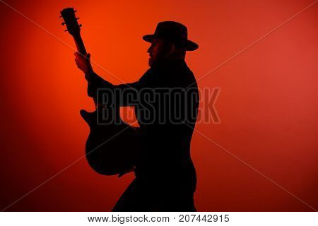silhouette of a musician playing instrument in a hat on a red background