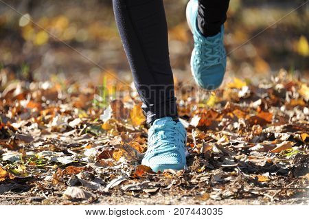 Young woman running outdoors in a autumn forest on a cold fall/winter day, lifestyle and healthy concept