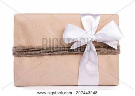 Christmas Gift Wrapped In Craft And Decorateed With Twine Tied In Band With White Silk Tape Isolated