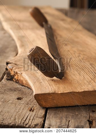 Old wood plane on a rustic oak plank wood working or carpentry background