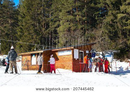 Bansko, Bulgaria - February 19, 2015: Skiers at the draglift in Bansko, Bulgaria.  Ski lift, pine trees and mountains view